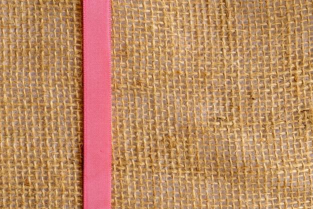 Różowa wstążka na jutowej tkaninie. pionowy