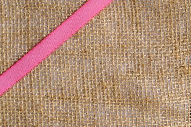 Różowa wstążka na jutowej tkaninie. przekątna