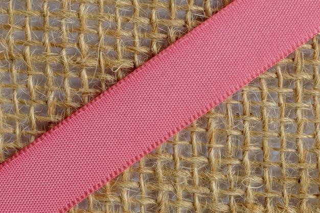 Różowa wstążka na jutowej tkaninie. skrzyżowane