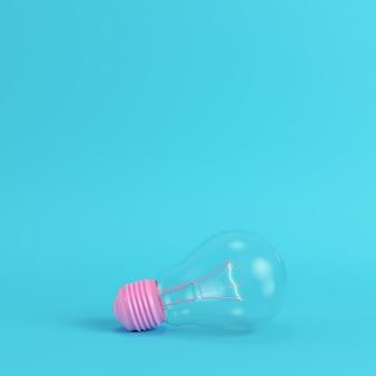 Różowa żarówka ze świecącą spiralą na jasnym niebieskim tle