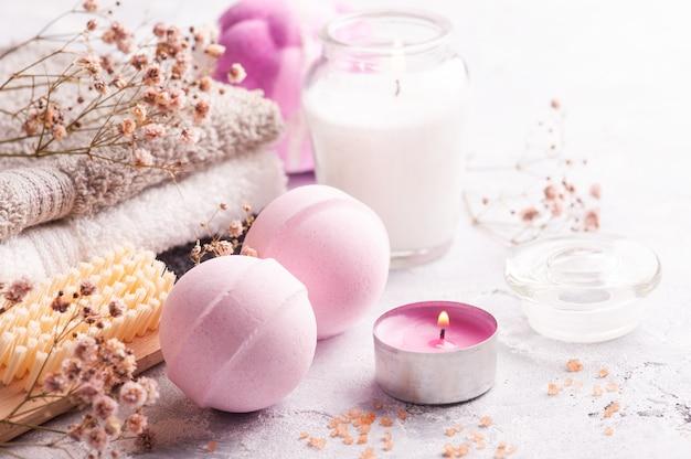 Różowe aromatyczne kule do kąpieli w aranżacji spa z suchymi kwiatami i zapaloną świecą