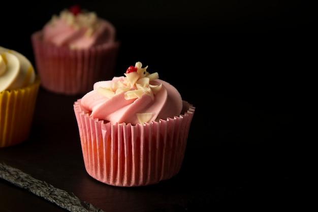 Różowe babeczki na czarnym tle, urodzinowych lub partyjnych babeczkach.