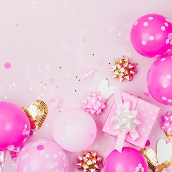 Różowe balony, prezent z konfetti, kokardkami i papierowymi dekoracjami. temat koncepcji przyjęcia urodzinowego. płaski układanie, widok z góry