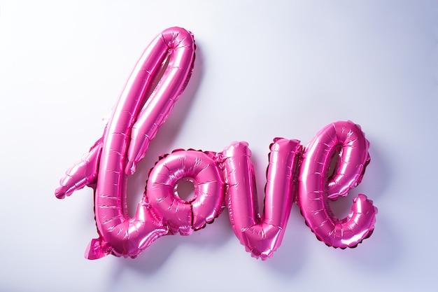 """Różowe balony w kształcie napisu """"love"""". walentynki. koncepcja miłości. wakacje. pt romansu. walentynki."""