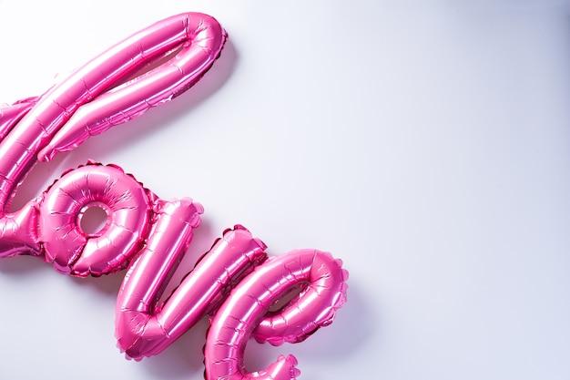 """Różowe balony w kształcie napisu """"love"""", z miejscem na tekst, leżące płasko. walentynki. koncepcja miłości. wakacje."""
