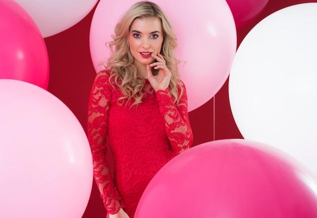 Różowe balony wokół atrakcyjnej kobiety