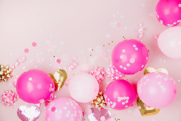 Różowe balony z konfetti, kokardkami i papierowymi dekoracjami. temat koncepcji przyjęcia urodzinowego. płaski układanie, widok z góry