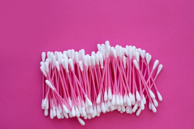 Różowe bawełniane pączki z białymi głowami ułożone na różowym tle