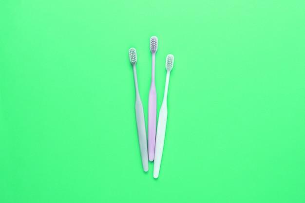 Różowe, białe i szare szczoteczki do zębów na zielonej ścianie.