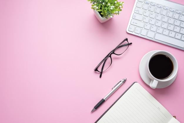 Różowe biurko biurowe z klawiaturą, okularami, kubkiem do kawy są umieszczone w biurze. skopiuj miejsce.