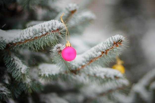 Różowe bombki choinkowe w kolorach flagi ukrainy. zabawka na zaśnieżonym drzewie