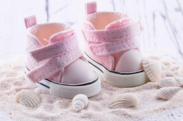 Różowe buciki dziecięce na białym piasku, muszelki