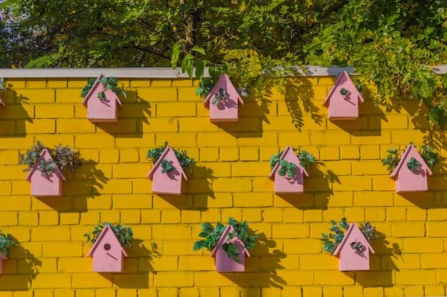 Różowe budki dla ptaków na żółtej ścianie