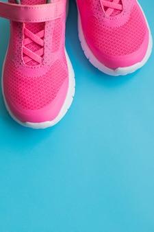 Różowe buty treningowe dla dzieci na białym tle na niebieskim tle. odzież dziecięca, odzież i moda dziecięca. sportowe tenisówki dla dzieci. para butów sportowych dziewczyna. skopiuj miejsce