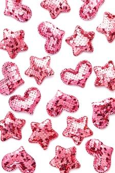 Różowe cekinowe serca i gwiazdy na białym stole.