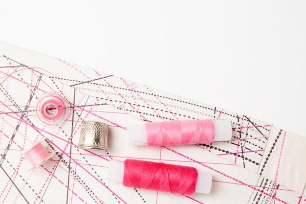 Różowe cewki nici i wzór oraz akcesoria do robótek ręcznych na białym tle