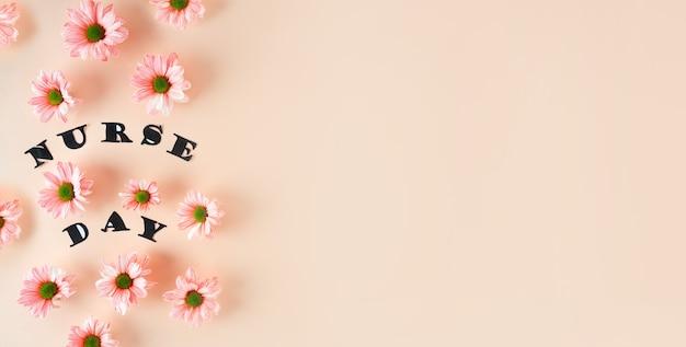 Różowe chryzantemy na pastelowym różowym tle i stylowe litery widok z góry z kwiatowym miejscem na kopię