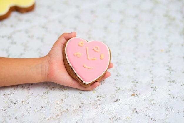 Różowe ciasteczka w formie serca leżą na dziecięcej ręce