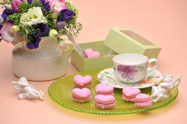 Różowe ciasteczka w kształcie serc na talerzu z aniołkami i kwiatami na walentynki