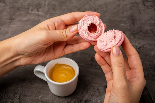 Różowe ciasteczko macaron jest złamane na pół w rękach kobiet