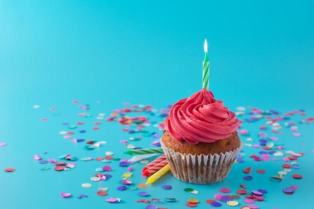 Różowe ciastko urodzinowe z zieloną świecą i konfetti na niebieskim tle