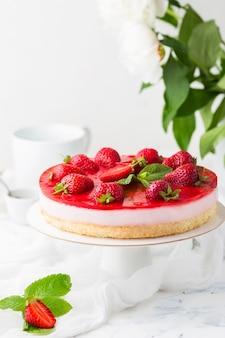 Różowe ciasto mus z galaretką jagodową ozdobione świeżymi truskawkami na stojaku z białym ciastem