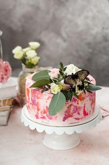 Różowe Ciasto Ozdobione Kwiatami I Prawdziwymi Motylami Podniosło Romantyczną Atmosferę Premium Zdjęcia