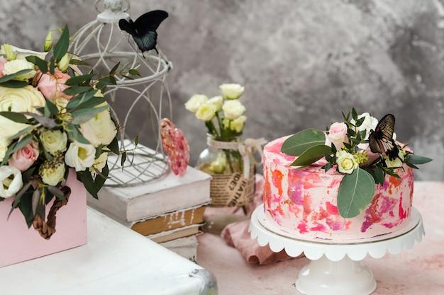 Różowe ciasto ozdobione kwiatami i prawdziwymi motylami podniosło romantyczną atmosferę