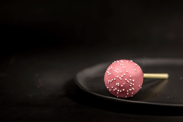 Różowe ciasto pop na czarnym talerzu