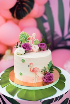 Różowe ciasto z flamingami na wakacje. ciasto z różnorodnymi dekoracjami, liśćmi palmowymi i świeżymi kwiatami.
