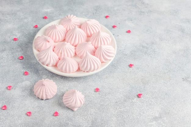 Różowe cukierki, cukierki, beza i cukier.