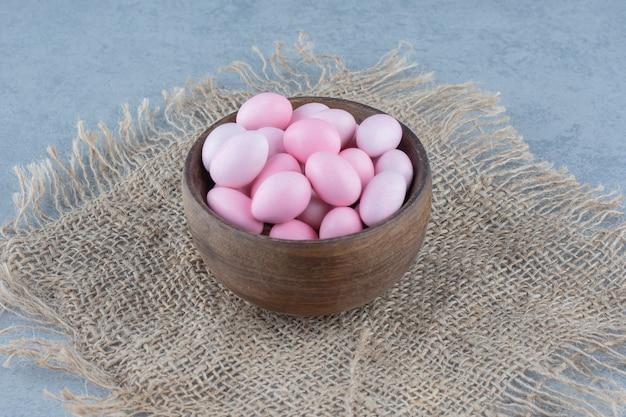 Różowe cukierki w filiżance na podstawce, na marmurowym stole.