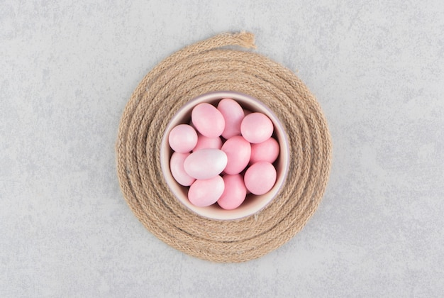 Różowe cukierki w filiżance na trójnogu na marmurowej powierzchni