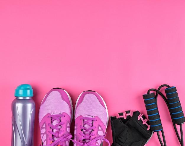 Różowe damskie tenisówki, butelka wody, rękawiczki i skakanka do uprawiania sportu