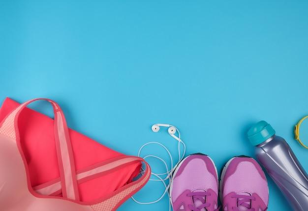Różowe damskie tenisówki, butelka wody, ubrania i staniki do uprawiania sportu
