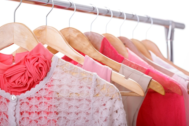 Różowe damskie ubrania na drewnianych wieszakach na stojaku na białym tle. szafy sukienki damskie, bluzki