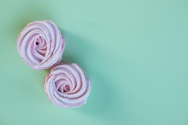 Różowe domowe pianki lub zefir. słodka, słodka pustynia nad pastelową zieloną ścianą. ciasteczka cukrowe. przestrzeń kosmiczna. zestaw suflet jagodowy, beza domowej roboty.