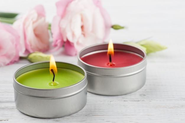 Różowe eustoma na białej drewnianej desce, zapalone świeczki