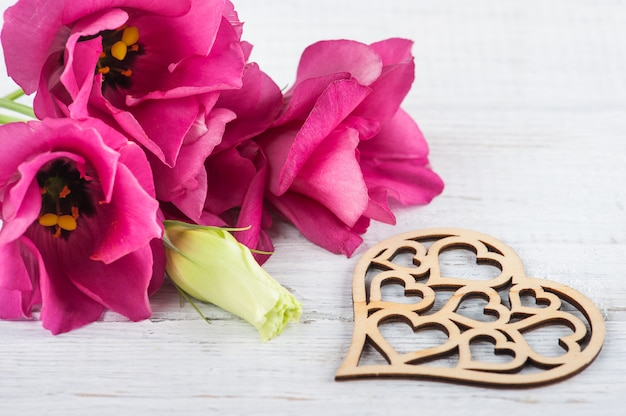 Różowe fioletowe kwiaty eustoma i drewniane serce