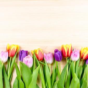 Różowe, fioletowe, żółte tulipany na drewnianym