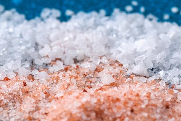 Różowe grube kryształy soli na niebieskim stole