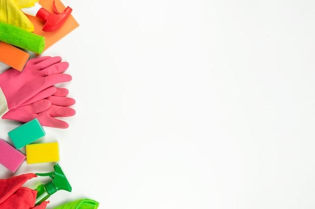 Różowe gumki, kolorowe gąbki i środki czystości leżą na białym stole w kuchni
