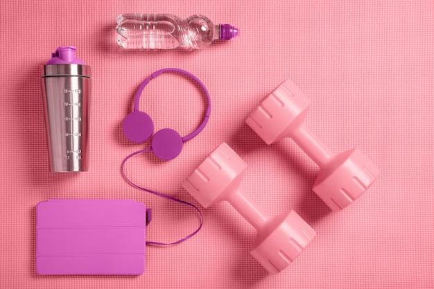 Różowe hantle, słuchawki i shaker proteinowy na macie fitness