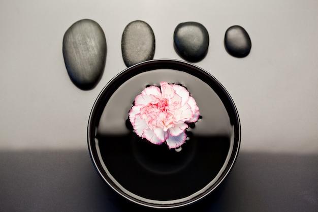 Różowe i białe goździki pływające w czarnej misce z wyrównanymi czarnymi kamykami nad nim