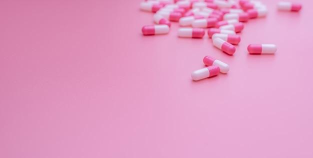 Różowe i białe kapsułki z antybiotykiem na różowym tle