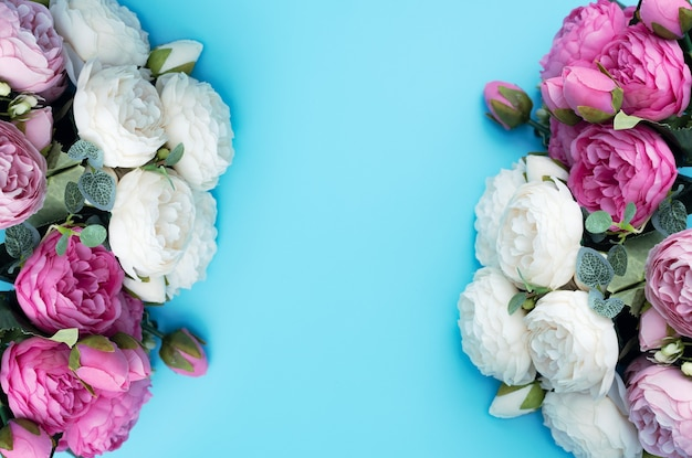 Różowe i białe kwiaty na niebieskim tle