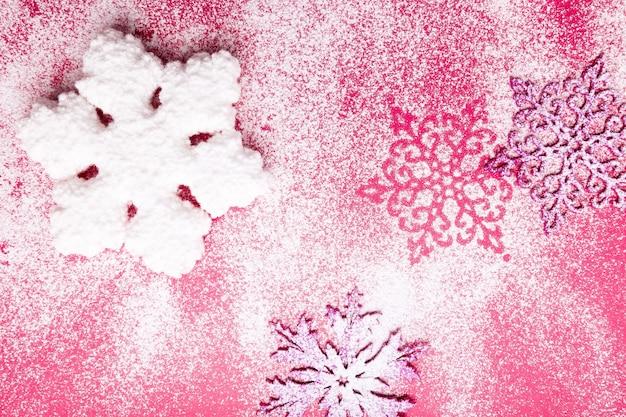 Różowe i białe płatki śniegu na różowym tle