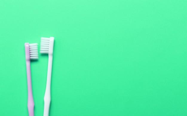 Różowe i białe szczoteczki do zębów na zielonej ścianie.
