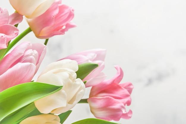 Różowe i białe tulipany na białym stole