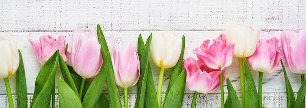 Różowe i białe tulipany na białym tle drewnianych. kwiatowy wzór. kartka z życzeniami. makieta. miejsce na tekst.